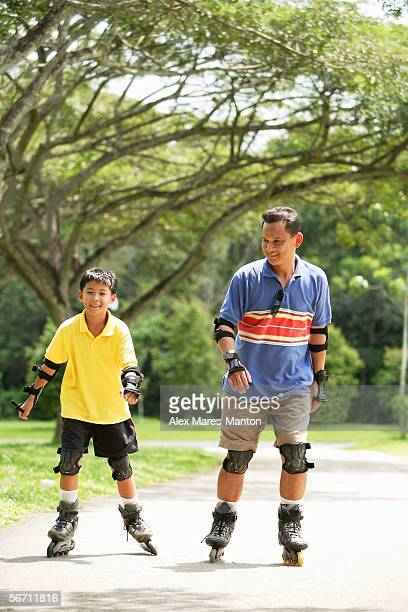 Father and son in park, on roller blades