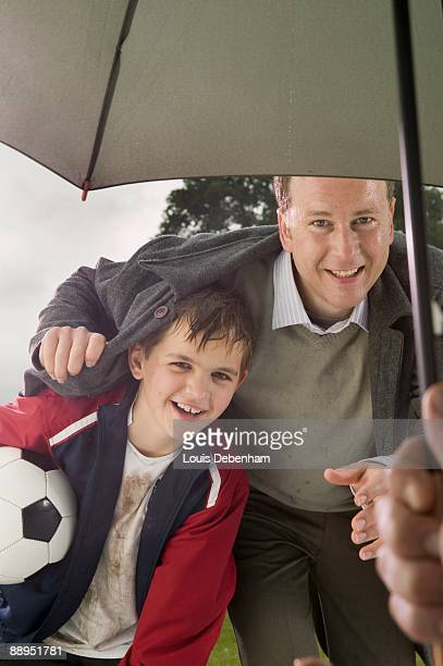 father and son in rain being offered shelter