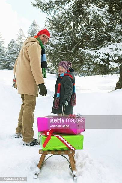 Father and son (8-10) in snow, boy pulling sledge, smiling, portrait