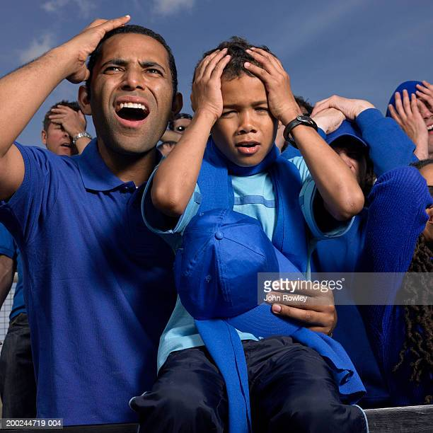 Padre e hijo (5-7) en estadio gente de a pie, las manos a la cabeza