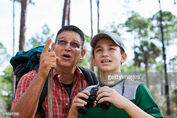 Father and son in woods with binoculars