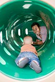 Father and son inside playground tunnel