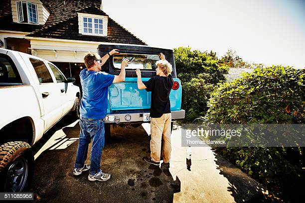 Father and son installing window truck restoration