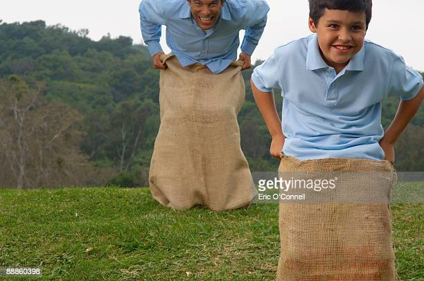Father and son jumping in potato sacks