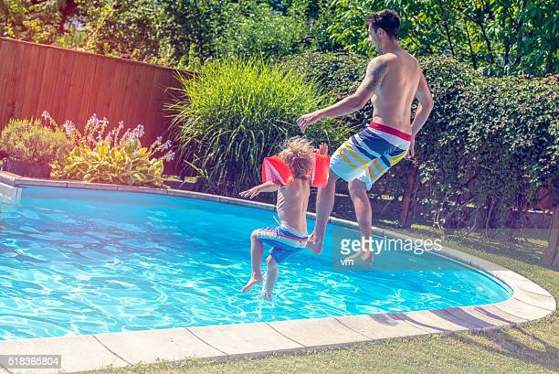 Father and son jumping into a pool