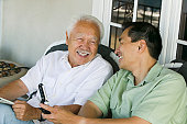 Father and Son Laughing and Using Cell Phone