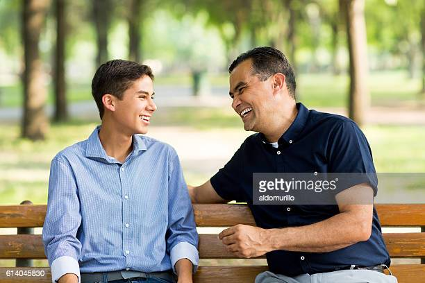 Father and son laughing on a bench