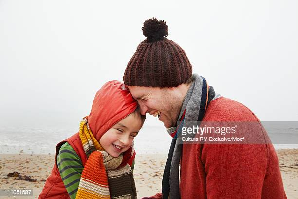 Father and son laughing on beach