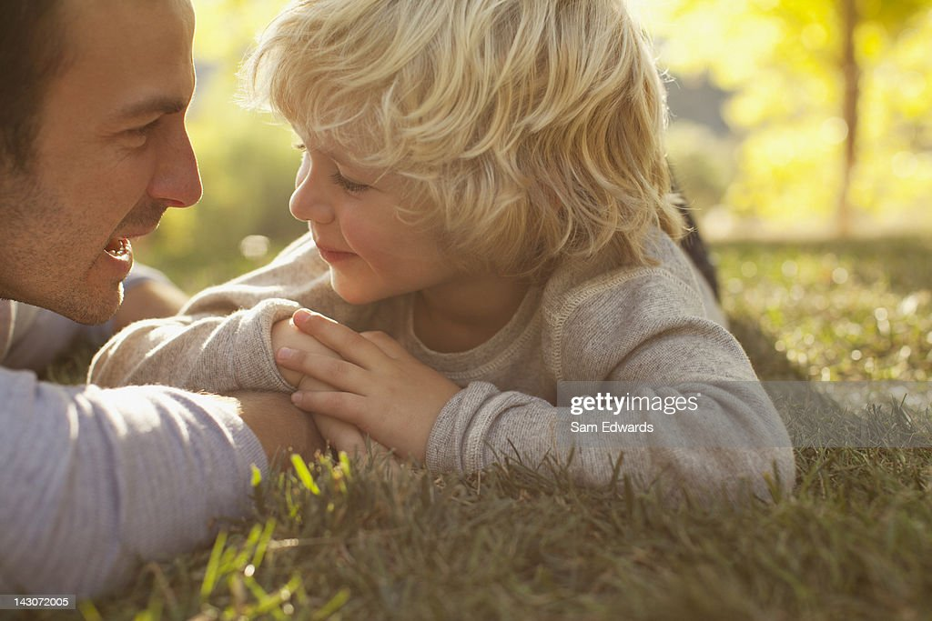 Father and son laying in grass together : Stock Photo