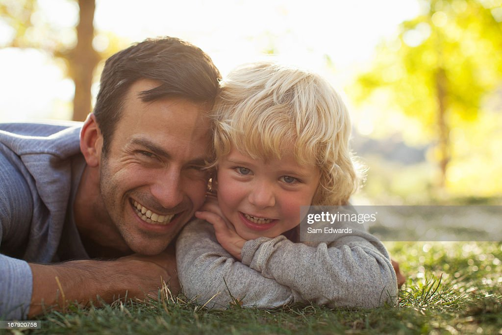 Father and son laying in grass together : Foto de stock