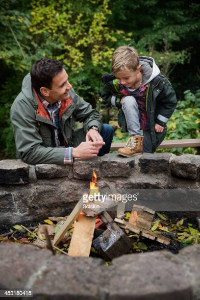 Father and son lighting a bonfire