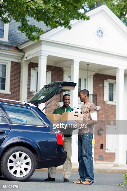 Father and Son Loading Car in Front of Dorm
