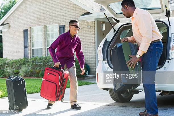 Father and son loading suitcases into car