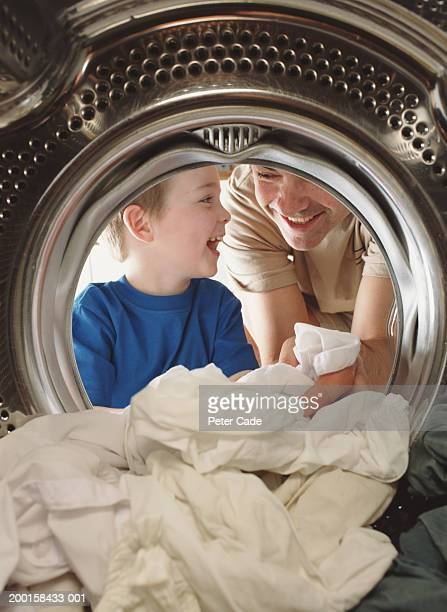 Father and son loading washing machine, smiling, view from inside drum