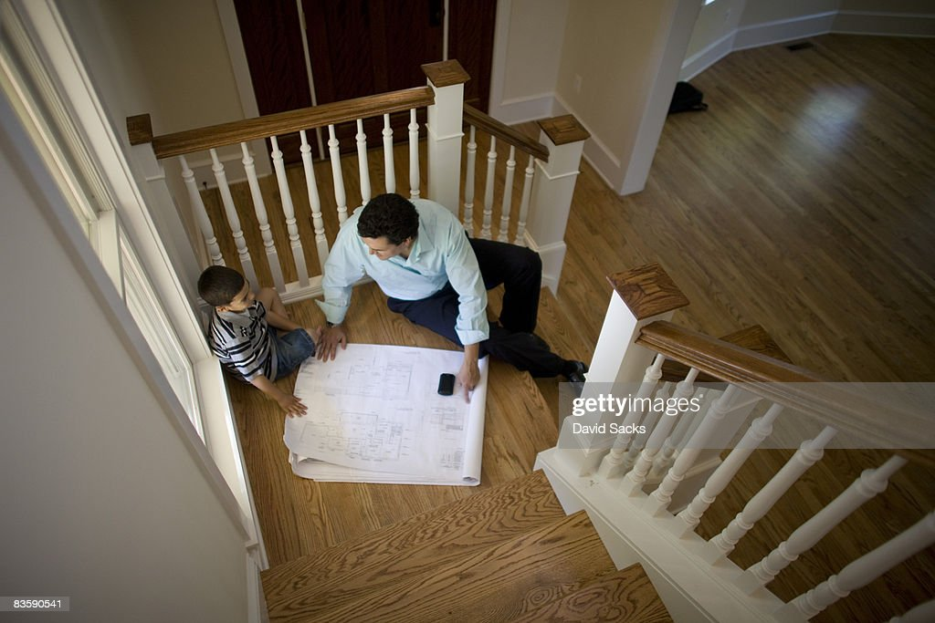 Father and son looking at blueprints : Stock Photo