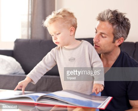 Father and son looking at book together : Stock Photo