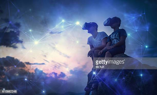 Father and son looking at futuristic network using VR glasses
