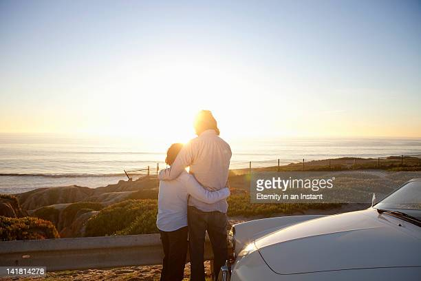 Father and son looking at ocean with sun flare