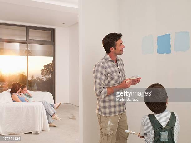 Père et fils à la recherche dans des échantillons de peinture sur le mur