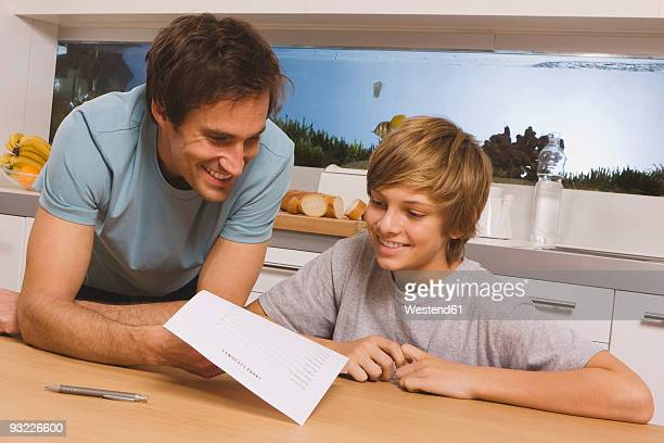 Father and son (14-15) looking at report card, smiling