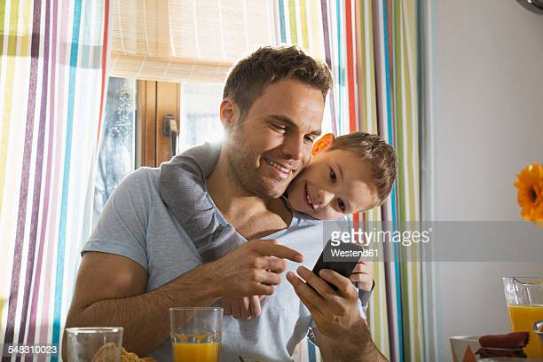 Father and son looking at smartphone
