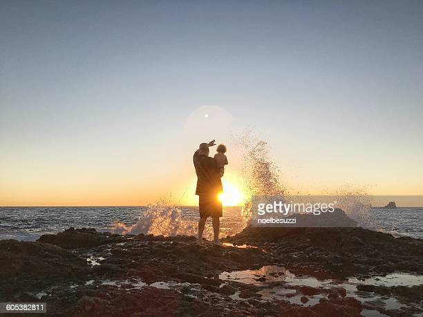 Father and son looking at sunset by beach