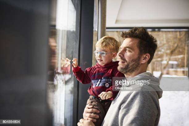 Father and son looking out of the window