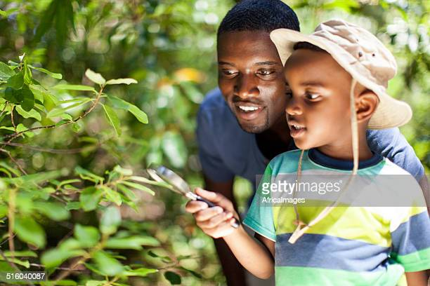 Father and son looking through a magnifying glass