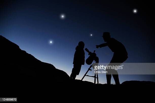 Father and Son looking through a telescope at nigh