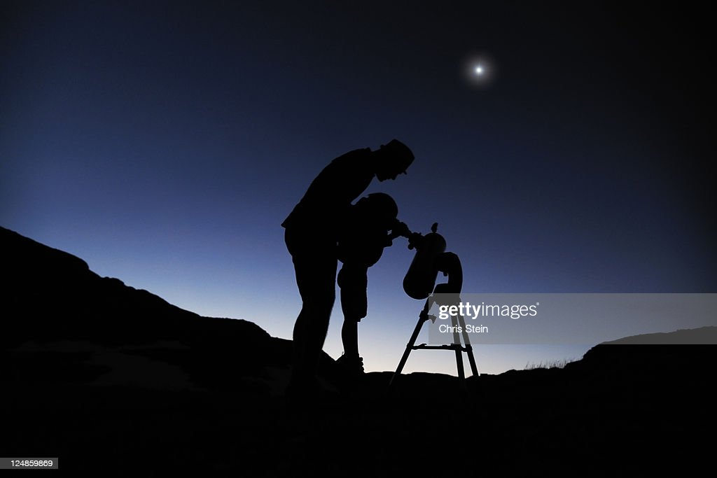 Father and son looking through a telescope : Stock Photo
