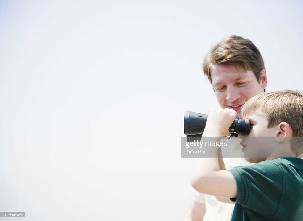 Father and son looking through binoculars : Stock Photo