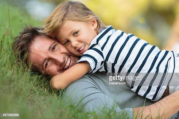 Vater und Sohn liegen auf dem gras