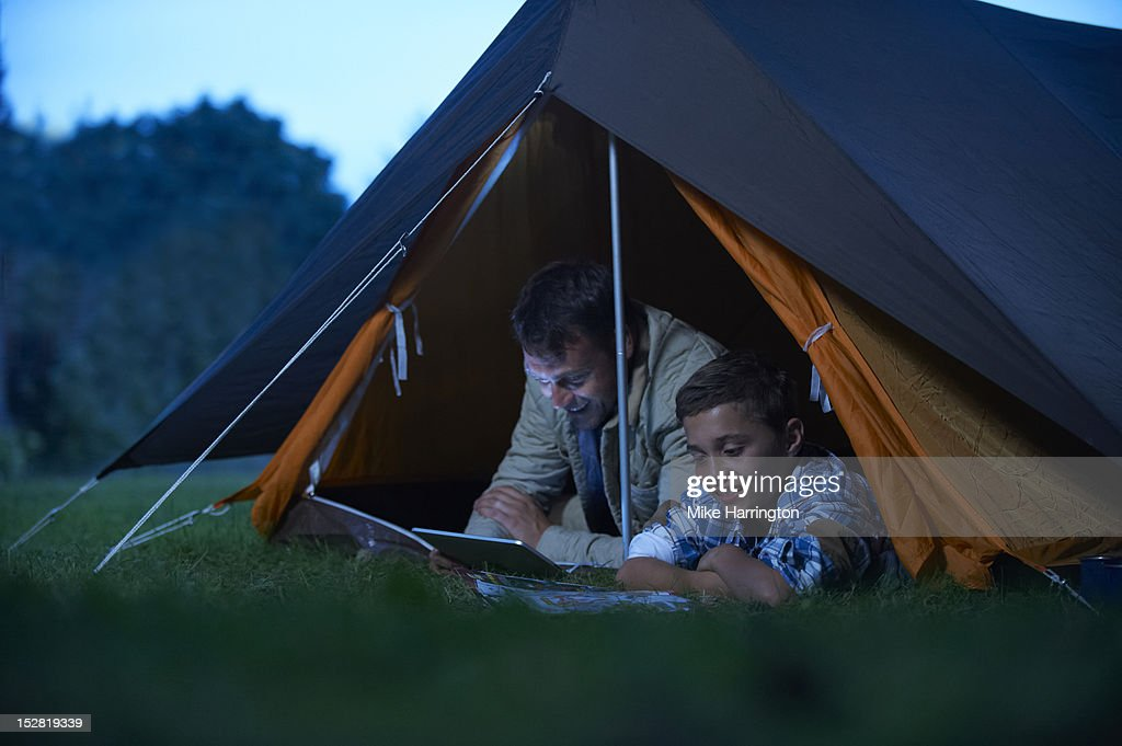 Father and son lying inside tent, reading. : Stock Photo