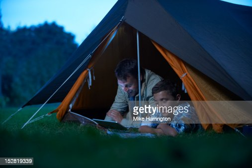 Father and son lying inside tent, reading. : Foto de stock