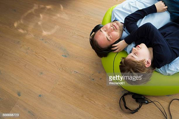 Father and son lying on bean bag in living room listening music