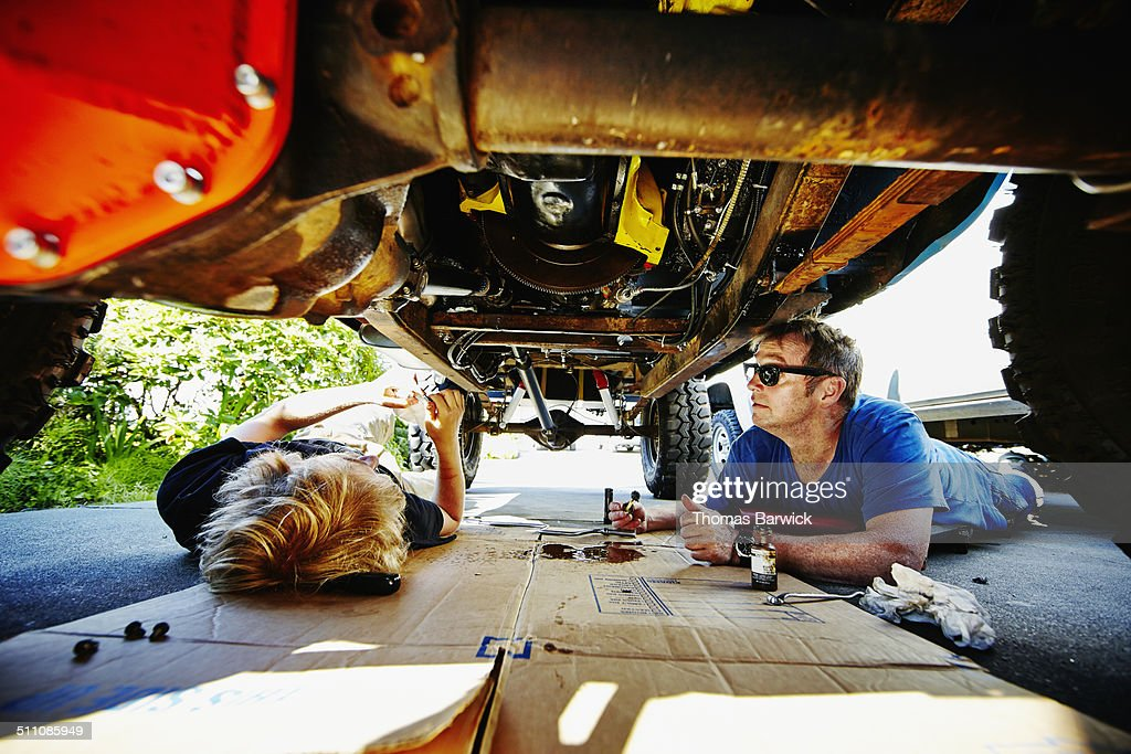 Father and son lying on driveway repairing vehicle : Stock Photo