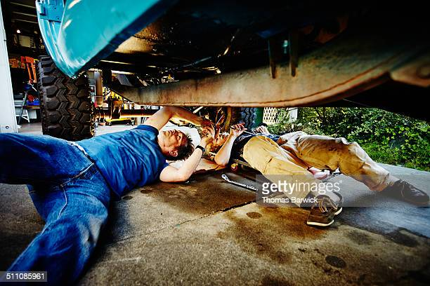 Father and son lying on driveway replacing oil pan