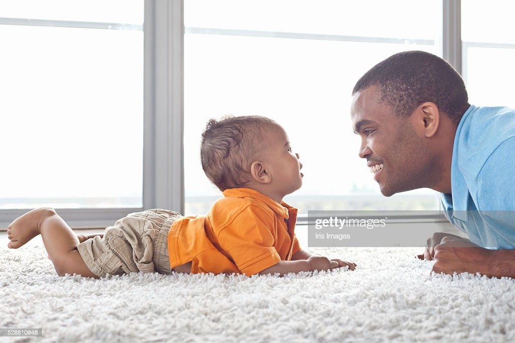 Father and son (6-12 months) lying on floor