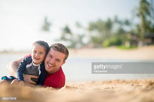 Father and Son Lying on the Beach