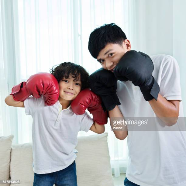 Father and son make faces with boxing gloves