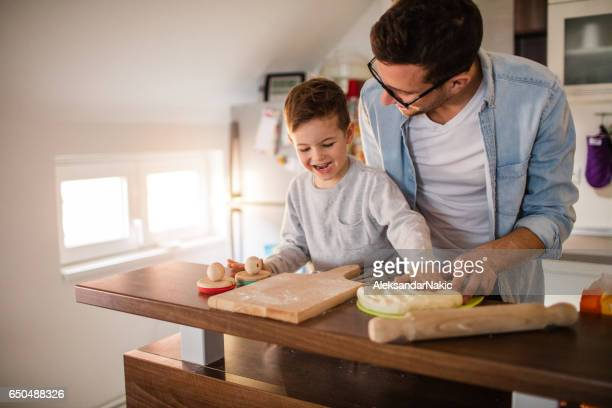 Father and son making a bread in the kitchen