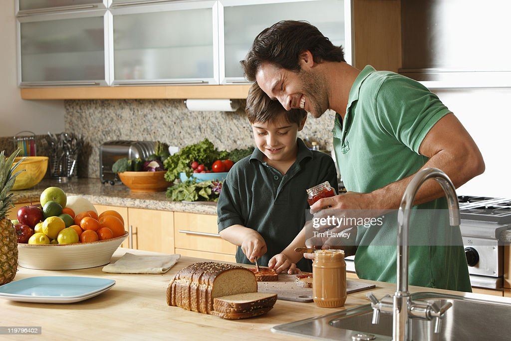 Father and son making peanut butter and jelly : Stock Photo