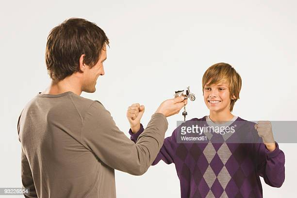 Father handing bike key to son (14-15)
