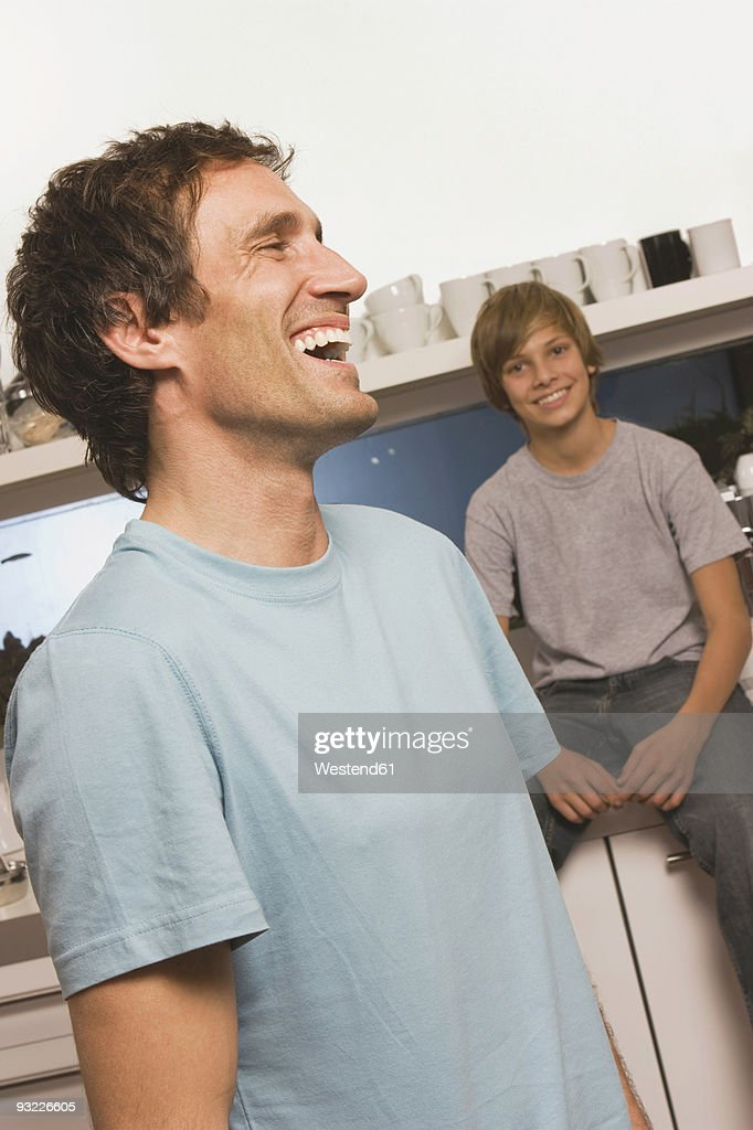 Father standing and laughing in kitchen, son (14-15) watching in background : Stock Photo