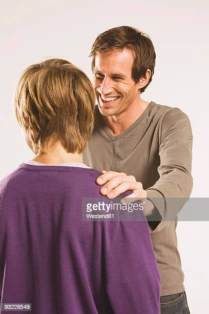 Father talking with son (14-15), laughing, close-up