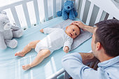 Father cuddle his baby son in bedroom, baby is in crib and enjoy in every moment
