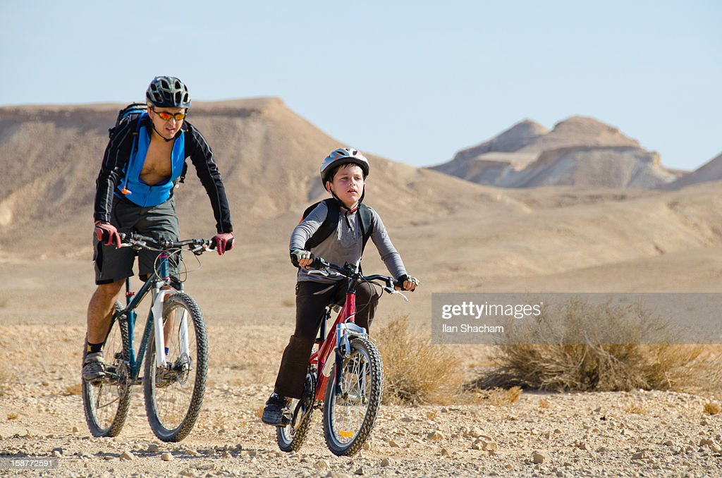 Father and son mountain biking together : Stock Photo