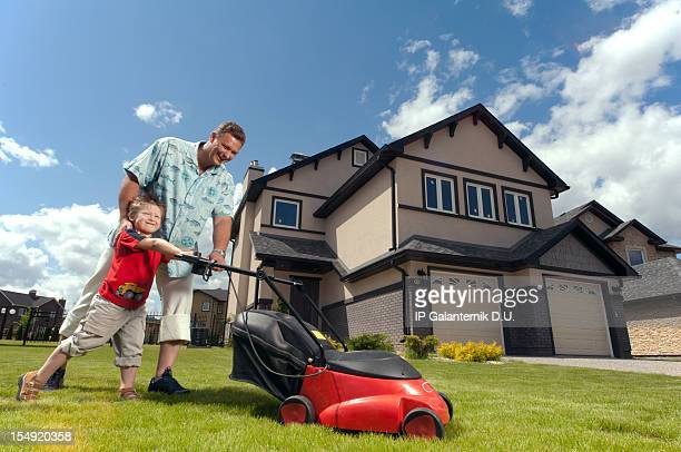 Father and son mowing in front of their suburban house.