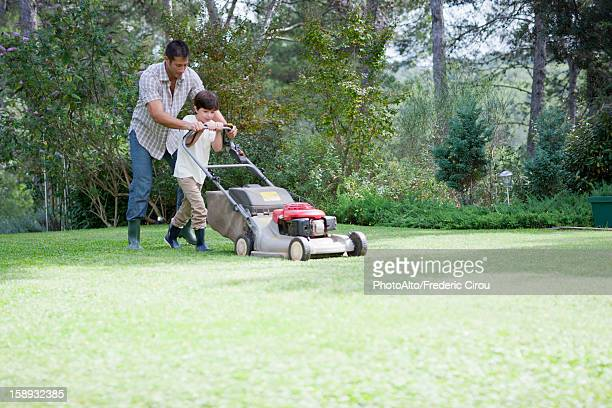 Father and son mowing lawn together