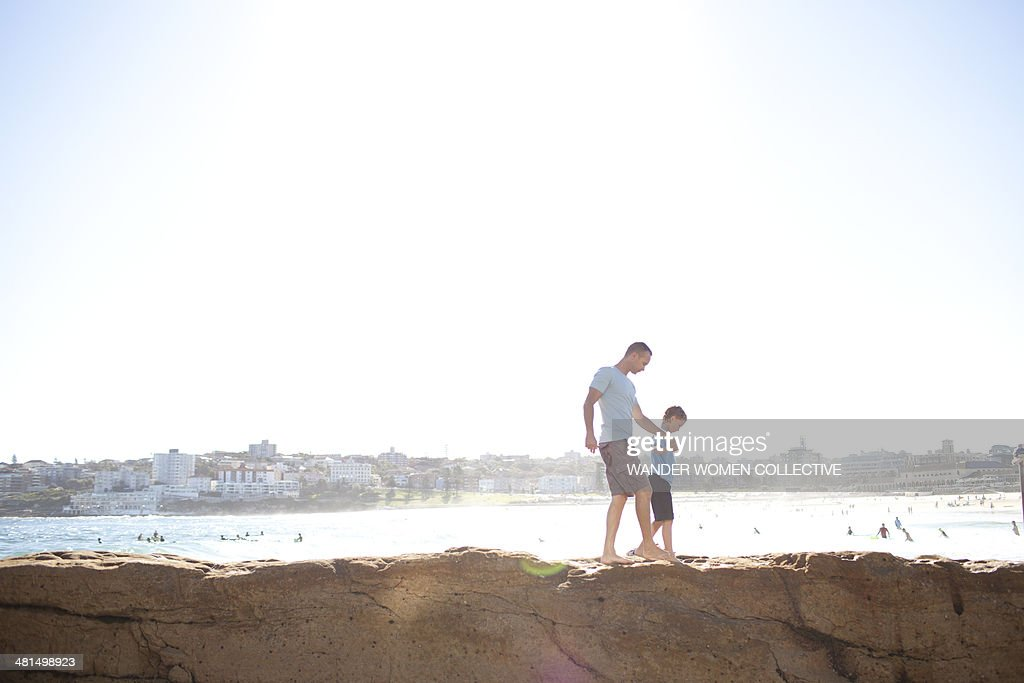 Father and son North Bondi walking on rocks : Stock Photo